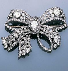A late Victorian diamond bow brooch, circa 1895, the triple looped tied ribbon bow, set with four principle old brilliant-cut diamonds amongst trailing leaf and bud foliage, between a continuous border of old brilliant-cut diamonds, diamonds approximately 10.00 carats total, later rhodium plated, width 5.1cm.