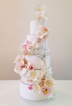 Ornately adorned wedding cake with sugar tassels and a cascade of confectionery blooms, including roses, tulips, peonies, and orchids | White Cakery Co.