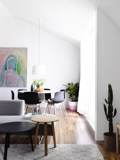 Small modern dining space with cacti and pastel artwork