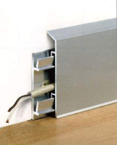 Rodapié de aluminio que alberga las conducciones eléctricas en su interior.