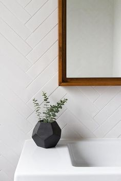 "Modern bathroom features walls clad in a white herringbone tiles, EliteTile Retro 2"" x 7-1/2"" Polished Soho Subway Porcelain Field Tile in White, lined with a West Elm Floating Wood Wall Mirror over a white porcelain wall-mount sink, Ceramica Tecla Serie 35 Ceramic Bathroom Sink with Overflow."