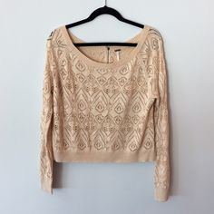 Free People Open Knit Zipper back top Pre-owned, great condition, no holes or stains. This is a size medium. Color is a peachy-cream-nude. Back zipper is functional and completely unzips. Made of 74% cotton/ 26% acrylic. Measurements: underarm to underarm flat across is approximately 21 inches. Top of shoulder to bottom of hem is approximately 21 inches. Free People Sweaters