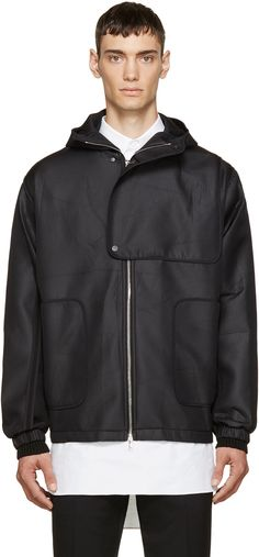 Long sleeve hooded jacket in black featuring exposed seams throughout. Layered panel at chest with press-stud closure. Two-way zip closure at front. Zippered patch pockets at waist. Elasticized cuffs. Bungee drawstring at hem. Bonded lining. Tonal stitching.