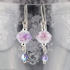 "Handmade lampwork glass bead earrings in white with sprinkles of pink and purple. Swarovski crystal in iridescent purple sparkles at the tip. Surgical steel ear wires. Approximately 41 mm (1.6"") from top of ear wire to tip of earring."