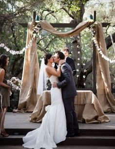 Create an easy rustic touch at your alter by draping burlap fabric across an arbor #wedding #ceremony #decorations
