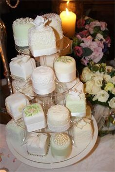 Miniature Wedding Cakes : Sugar covered cakes, decorated with hand piping, sugar roses, sugar pearls and hand painting in cocoa butter, finished with ribbons and lace