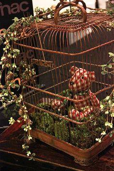 Solte os passarinhos e use a gaiola para decorar a festa de Natal. Aqui, virou um jardim para o urso de pano