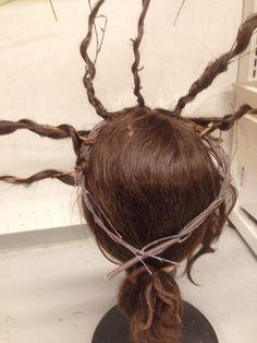 """Først bør man lage en bøyle/krans av greiner eller teipet ståltråd, og deretter feste de utstående greinene på denne med håret tvinnet rundt. Greinene bør stå tettere og være av en litt mer """"snirklete"""" type. Jeg har brukt bomullstråd og ullgarn for å feste håret fast."""
