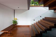"""Esta """"casa varanda"""" se distribui em três andares num terreno de acentuado declive. Suas grandes portas de vidro permitem o contato visual com o mar."""