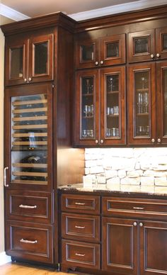 Custom Kitchen Cabinets by Walker Woodworking Lots of glass doors in this wet bar design. Love that rock splash, a great contrast with the dark stained cabinets. #design #ideas