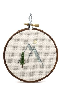 """Here in the PNW we love the outdoors but we can't get out there all the time. This little cross stitch is perfect for bringing some calm to an office or apartment. Dimensions: Measures 3"""" across. Deta"""