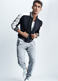 Keep your outfit laid-back in a monochrome baseball jacket and grey jogging pants. Round off this look with white high top sneakers.  Shop this look for $100:  http://lookastic.com/men/looks/black-and-white-varsity-jacket-white-crew-neck-t-shirt-grey-sweatpants-white-high-top-sneakers/6314  — Black and White Varsity Jacket  — White Crew-neck T-shirt  — Grey Sweatpants  — White High Top Sneakers