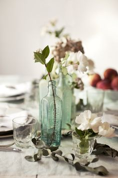 .simple wedding table flowers, upcycled bottles, single flower clippings, elegantly simple, keep cost of decorating down