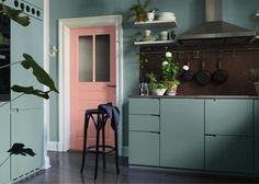 A porta de entrada desta cozinha azul surpreende com um rosa, temperando diversão no espaço de tons sóbrios.