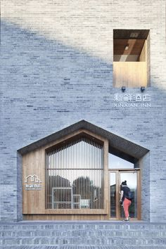 A gabled opening that references the forms of traditional hutong houses marks the entrance to this hotel in Beijing by architecture studio Penda.