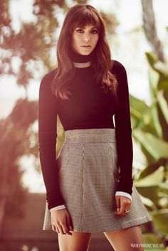 Nina Dobrev wears a turtleneck sweater, houndstooth miniskirt, and delicate rings, photographed by Zoey Grossman