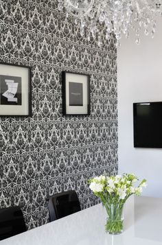 Black White Ornate Vintage Decorative Wallpaper In The Meeting Room With Wall Frames Along With Modern Meeting Set And Mounting Tv Also Crystal Chendelier And Fresh Flower Decoration Interior Design Office in Black and White http://seekayem.com