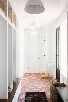 Clad in red herringbone brick floor tiles, this stunning long mudroom is illuminated by three white industrial pendants hung from a shiplap ceiling in front of a glass paneled black door positioned facing open lockers fitted with white pull out drawers positioned beneath a a wood bench located under  overhead shelves holding dip dyed baskets.