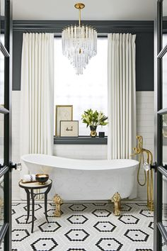 glamorous bathroom with black and white tiles and roll top bath with gold fixtures