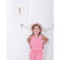 Les stickers A3 guirlande noeuds et étoiles Flamingo by Lucie Bellion pour Lilipinso aux tonalités de rose et de doré apportent un décor chic à la chambre d'une petite fille.