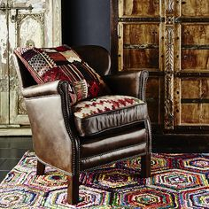 Cavendish Armchair | An elegant armchair, richly upholstered with reversible seat, upholstered in distressed vintage cigar leather and kilim fabric, finished with antique style studding, with wood feet, ensuring an ideal choice for any classical living room.