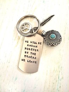 Inspirational keychain, quote keychain, bohemian keychain, hippie keychain, hand stamped keychain, motivational gift.  I absolutely love this hand stamped inspirational keychain. The silver tone blank is stamped with we will be known forever by the tracks we leave. Included on the keychain are a decorative canteen, a small feather and a peace sign. The keychain measures about 3 inches.  All my keychains come in a gift box ready for gift giving.  Check out my other keychains here…