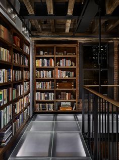 Library space suspended above the main living area on a metal and glass gallery walkway - 10 Hubert Street New York. Conservation project, restoring a dilapidated building in the TriBeCa area creating a beautiful three storey penthouse.