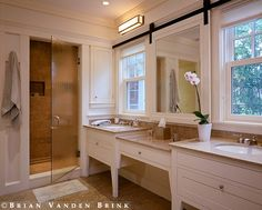 Windows in front of bath vanity sinks - note how the mirror is mounted on a sliding barn-door track to give it freedom of location, also to hide a window? Great idea! Design: Hutker Architects. photo by Brian Vanden Brink.