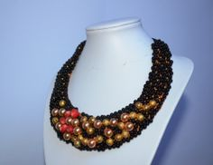 Statement necklace, handmade, with golden pearls, golden stardust, black glass beads. For sale.