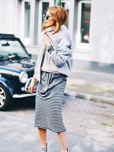 Fashion blogger Maja Wyh is wearing a striped skirt with an oversized long sleeve top and a grey teddy jacket. | @andwhatelse