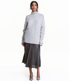 Sort/Sølv. Plisseret nederdel til midt på læggen i vævet kvalitet med glitrende folieprint. Nederdelen har elastik i taljen og er foret med kort underskørt