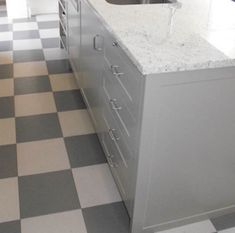 The gray-and-white checkerboard pattern of these tiles (from Cork Concepts) mirrors the kitchen's modern, rectilinear aesthetic.