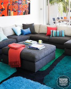 A Montana modular sofa in steely charcoal from Jardan is big enough for the whole family and is offset by colourful plain silk cushions from Cambodia House.
