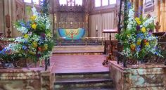 Large hanging flower arrangements of country garden flowers on the screen at All Saint's Parish Church, Leamington Spa