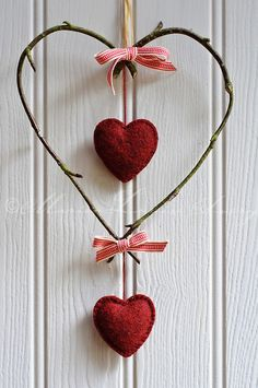 Decorative heart made of birch twigs tied with woven red and white ribbon with hanging red felt hearts
