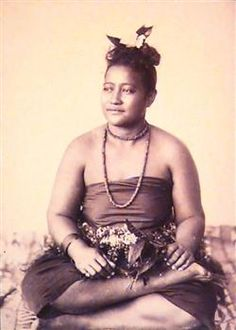 An unknown woman sits cross-legged on siapo (decorated tapa cloth) holding a flower stalk in her left hand. She has a dark strapless garment with a titi, a cobra-style necklace in two strands and her hair is up (flower visible in her hair). Woman is looking slightly to the (viewers') left. Andrew, Thomas Photographer  1890 - 1910