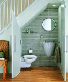 Inspiring Tiny Bathroom Under Stairs As Space Saving Design With Unique Wall Mount Sink And Circle Bath Mirror And Green Ceramic Wall Tile On Wooden Floors Designs