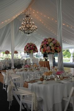 wedding tent... Love the chandelier, not so much on the tall centerpieces...
