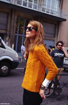 We love the messy do, mustard cable knit sweater, and oversized sunnies. Tres chic!