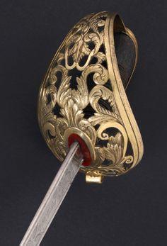 """R-908G12.- Sable para oficial de Caballería ligera, modelo 1840. España, fechado 1854. Guarnición en latón, versión de cazoleta calada. Monterilla  larga marcada """"O. de C."""". Hilo y torzal de cobre afirmando la piel de lija que cubre la madera del puño. Hoja curva, dos canales, decorada en ambos costados. Inscripciones: """"Art. Fca. de Toledo"""" - """"Año de 1854"""". Vaina de hierro. Long. Total: 104 cms; Long.Hoja : 88,5 cms; Anchura base hoja: 23 mm Toledo Sword, Chopper, Weapons, Blade, Door Handles, Weapons Guns, Swords, Cold Steel, 19th Century"""