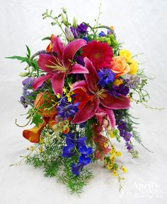 Gorgeous colorful cascade style bridal bouquet! Filled with lilies, delphinium, calla lilies, gerbera daisies and oncidium orchids. Flower's by April's Garden in Durango,CO http://www.durangoflorist.com/