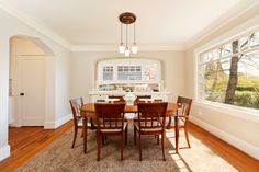 Red wood rounded table, chairs & flooring with carpet on. White wall & ceiling with arc entry with wide open glass window.