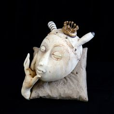 "Lisa Clague - Crimson Laurel Gallery, Bakersville NC - Sculpture, Ceramics ""Resting Rabbit Queen"",  Ceramic, 4.5 x 3 x 4 in,  Concrete Pillow. Finishes with graphite drawing, oxides, wax, with gold luster. Low fired and Mid range firings."