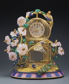 "PATEK PHILIPPE ""THE HUMMINGBIRD CAGE CLOCK"" A MAGNIFICENT AND STUNNING YELLOW GOLD, SILVER, DIAMOND, SAPPHIRE, YELLOW SAPPHIRE, PINK TOURMALINE, MOTHER-OF-PEARL, ROSE QUARTZ, CHALCEDONY AND LAPIS LAZULI CLOCK. --Sotheby's"