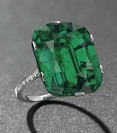 AN EXCEPTIONAL EMERALD AND DIAMOND RING   Set with a cushion-shaped emerald, weighing approximately 23.28 carats, to the diamond line shoulders, mounted in platinum
