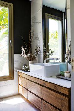 Toilette bohemio y moderno con piso de porcelanato 'Calacatta Lucido' (SBG), bacha 'Country Alta' (Ferrum), grifería 'Libby' monocomando (FV) y espejo biselado sobre marco de acero inoxidable (Cristal Box). El mueble es de petiribí con mesada en Silestone 'Blanco Zeus'.