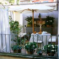 outdoor room dressed in white ~ a charming balcony with greenery