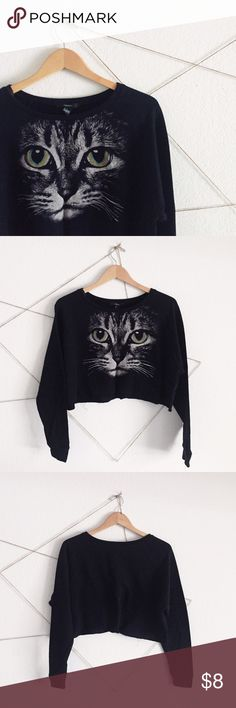 Cat Graphic Long Sleeve Crop Top A black cropped long sleeve with a cat face graphic printed in the front. The cat print is in a muted white with colored eyes and has a great vintage look to it thanks to the coloration of print and the unfinished edges at the bottom seams. Great to lounge around in or wear out. Only worn twice! 45% cotton, 45% polyester. Not from Urban Outfitters, just listed for exposure. Actually from Forever 21. Urban Outfitters Tops Tees - Long Sleeve
