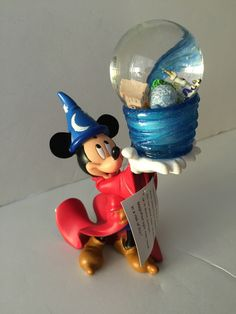 Sorcerer Mickey holds the Magic of Walt Disney World in his hand. Shake to send symbols of the Four Parks swirling inside the snowglobe amidst cascading glitter. This Mickey Mouse Snowglobe is a great