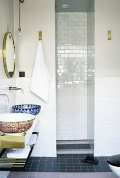 Bathroom with subway tile, brass mirror and hooks, and beautiful colorful sink basins